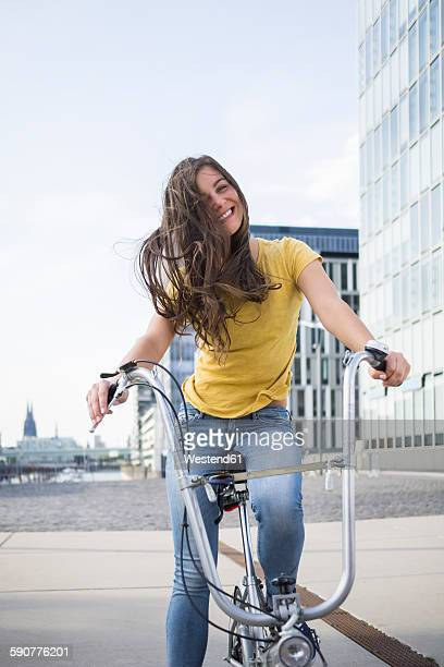 Germany, Cologne, portrait of smiling young woman with blowing hair on her bicycle