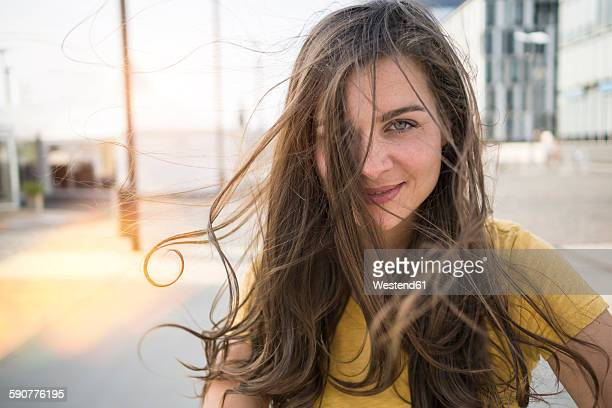 germany, cologne, portrait of smiling young woman with blowing hair - only young women stock pictures, royalty-free photos & images
