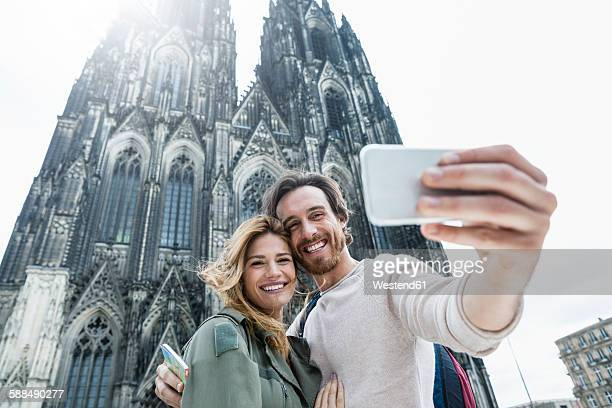 germany, cologne, portrait of young couple taking a selfie in front of cologne cathedral - cologne cathedral stock photos and pictures