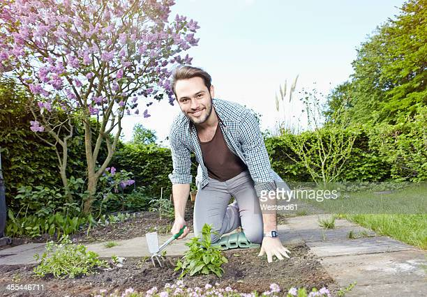 Germany, Cologne, Portrait of young man gardening patch, smiling
