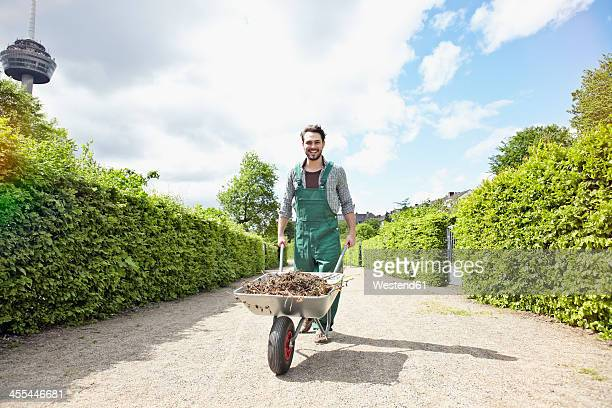 Germany, Cologne, Portrait of young man holding wheelbarrow, smiling