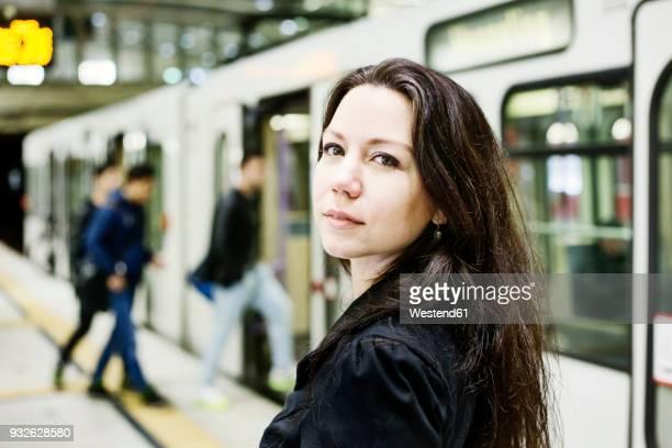 germany, cologne, portrait of young woman at underground station platform - bahnreisender stock-fotos und bilder
