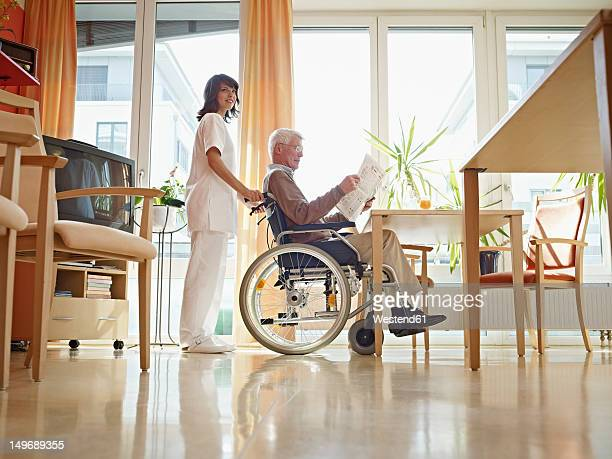 Germany, Cologne, Senior man reading newspaper in wheelchair, caretaker standing beside