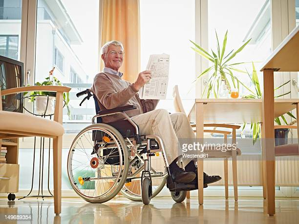 Germany, Cologne, Senior man reading newspaper in wheelchair