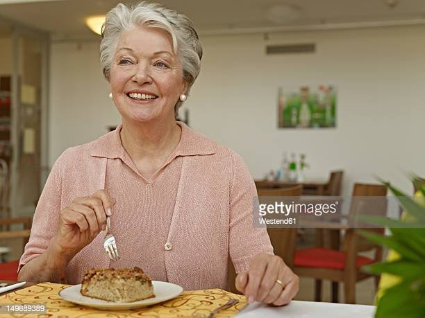 Germany, Cologne, Senior woman eating at table in nursing home