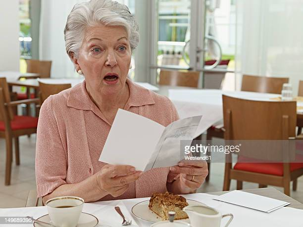 Germany, Cologne, Senior woman with card in nursing home