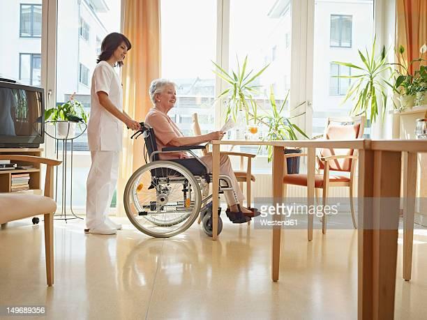 Germany, Cologne, Senior women reading newspaper in wheelchair, Caretaker standing beside