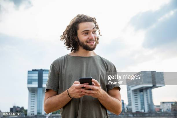 germany, cologne, smiling young man holding cell phone looking sideways - alleen één jonge man stockfoto's en -beelden