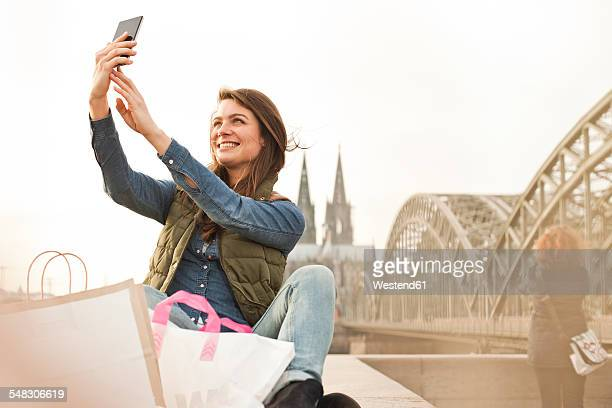 Germany, Cologne, smiling young woman with shopping bags taking a selfie