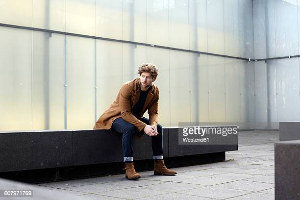 Germany, Cologne, stylish young man waiting on a stone bench