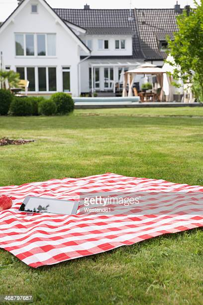 Germany, Cologne, Tablet pc on blanket in garden