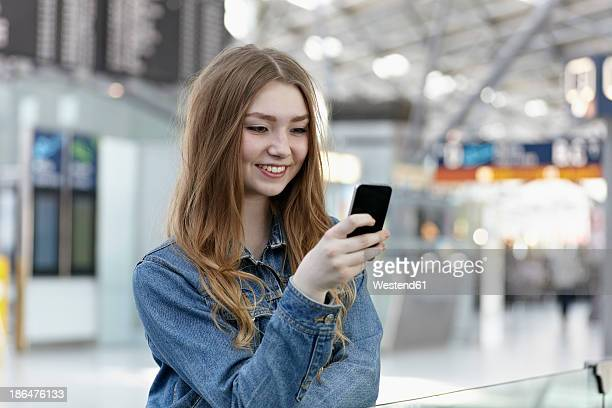 Germany, Cologne, Teenage girl holding mobile at airport
