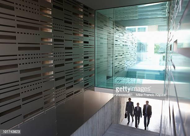 germany, cologne, three business people in staircase, elevated view - eintreten stock-fotos und bilder