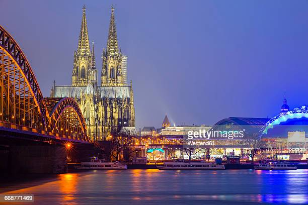 germany, cologne, view to lighted cologne cathedral with hohenzollern bridge in the foreground - cologne cathedral stock photos and pictures