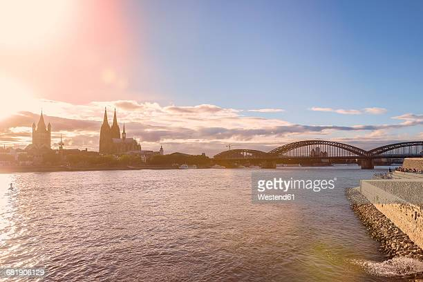 Germany, Cologne, view to the city with Rhine River in the foreground at evening twilight