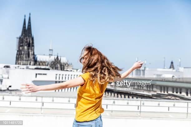 germany, cologne, woman dancing on roof terrrace - cologne stock pictures, royalty-free photos & images