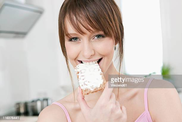 Germany, Cologne, Woman eating bread