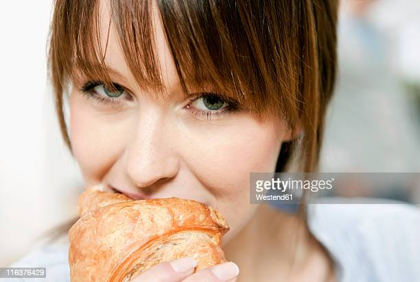 Germany, Cologne, Woman eating croissant