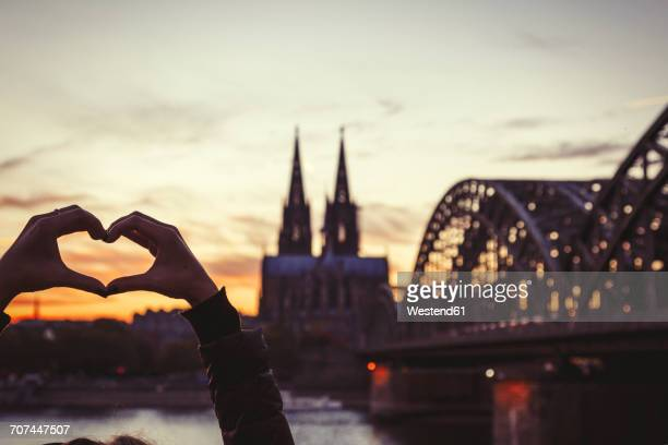 germany, cologne, woman shaping heart with her hands in front of cologne cathedral and hohenzollern bridge at dusk - cologne stock pictures, royalty-free photos & images