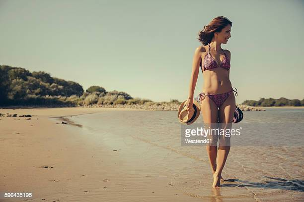 Germany, Cologne, woman walking on the beach along waterside of Rhine River
