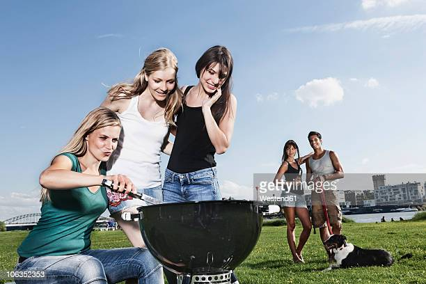germany, cologne, women barbecueing and friends in background with dog - zakelijke kleding stock pictures, royalty-free photos & images