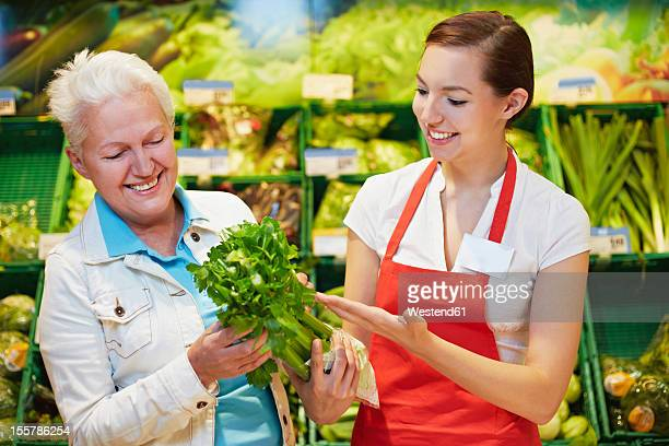 Germany, Cologne, Womens with celery in supermarket