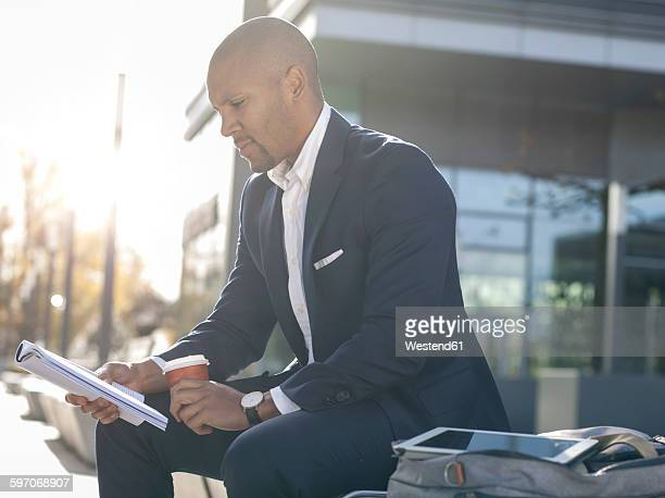 germany, cologne, young businessman sitting on bench, reading magazine - mixed magazine stock photos and pictures