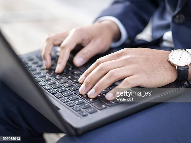 Germany, Cologne, Young businessman typing on laptop, close up
