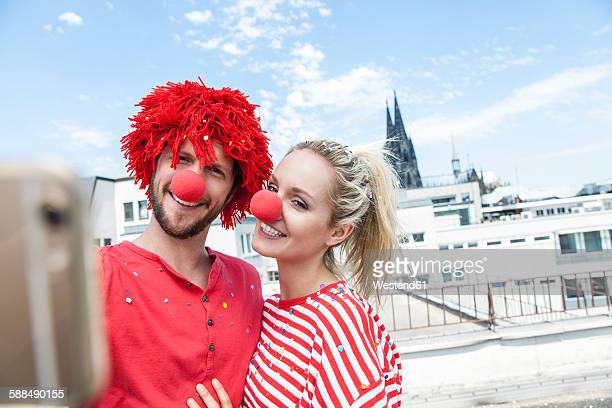 germany, cologne, young couple celebrating carnival dressed up as clowns - clown's nose stock photos and pictures