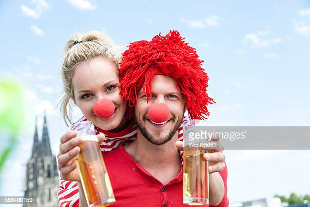 germany, cologne, young couple celebrating carnival dressed up as clowns - karneval stock-fotos und bilder