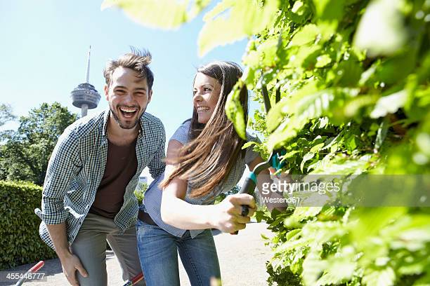 Germany, Cologne, Young couple cutting leaves with shears, smiling