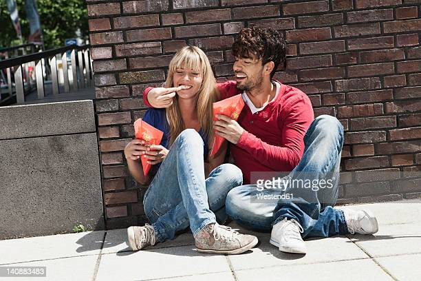 Germany, Cologne, Young couple eating french fries, smiling