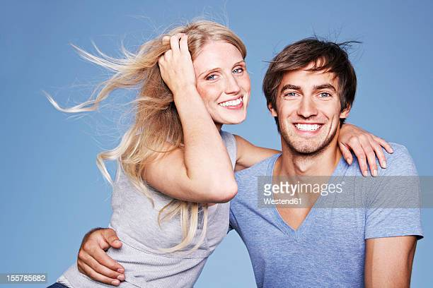 Germany, Cologne, Young couple embracing, smiling, portrait