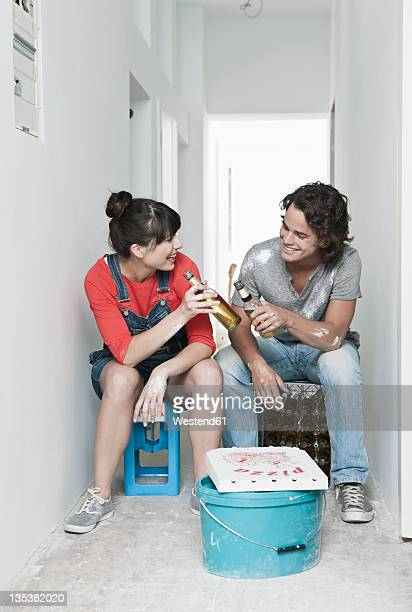 Germany, Cologne, Young couple having lunch break in renovating apartment