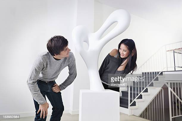 Germany, Cologne, Young couple standing in art gallery, smiling