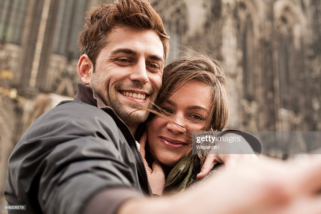 Germany, Cologne, young couple taking selfie in front of Cologne Cathedral : Stock-Foto