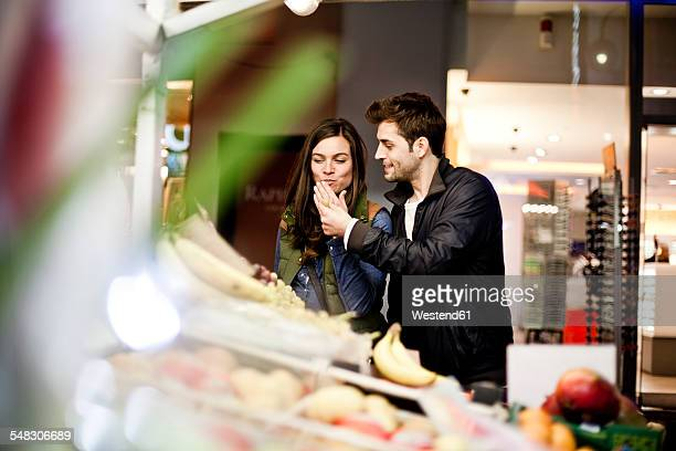Germany, Cologne, young couple tasting fruits at grocery stand