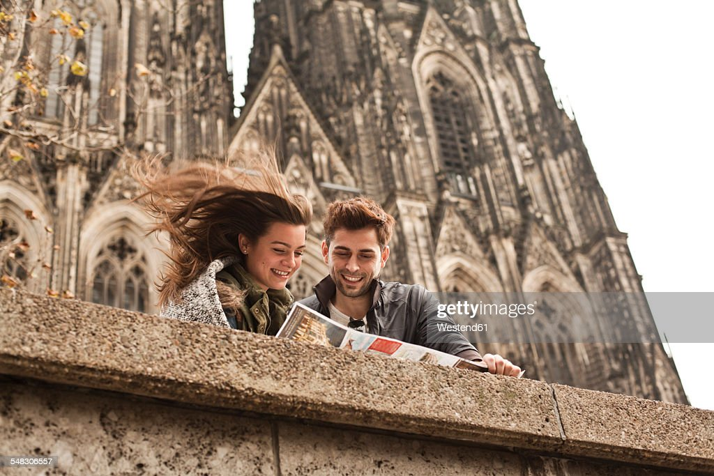 Germany, Cologne, young couple watching city map in front of Cologne Cathedral : Stock Photo
