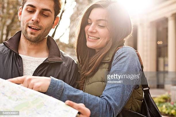 Germany, Cologne, young couple watching city map