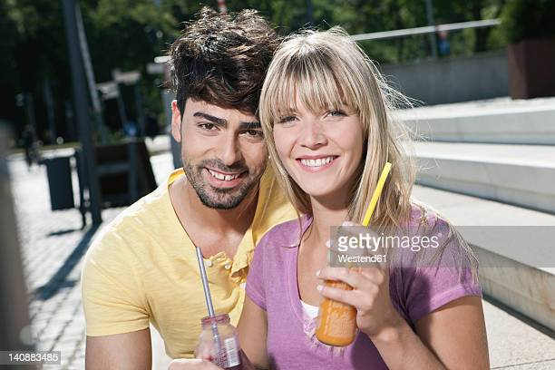 Germany, Cologne, Young couple with drink, smiling, portrait