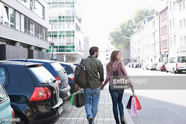 Germany, Cologne, Young couple with shopping bags near parking lot, smiling