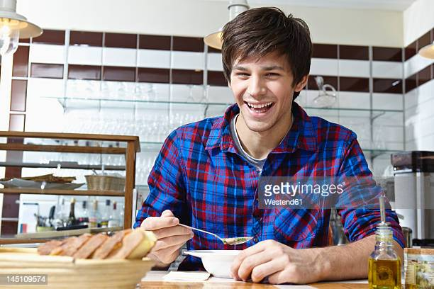 Germany, Cologne, Young man eating food, smiling, portrait