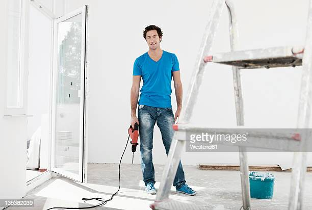 Germany, Cologne, Young man holding electric drill in renovating apartment
