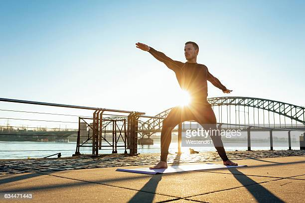 Germany, Cologne, Young man practicing yoga at the riverside