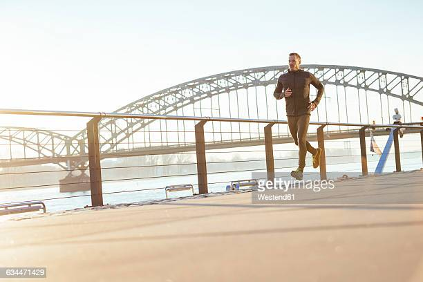 Germany, Cologne, Young man running at the riverside