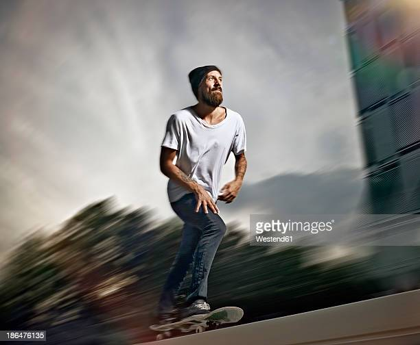 Germany, Cologne, Young man skating on skateboard