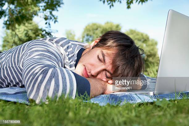germany, cologne, young man sleeping in meadow - 腹ばい ストックフォトと画像