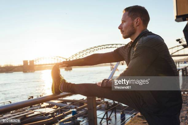 germany, cologne, young man worming up for workout - human leg stock pictures, royalty-free photos & images