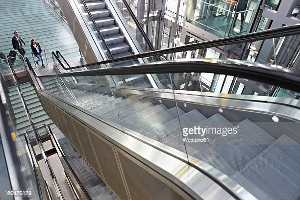 Germany, Cologne, Young woman and mature man moving up escalator   at airport