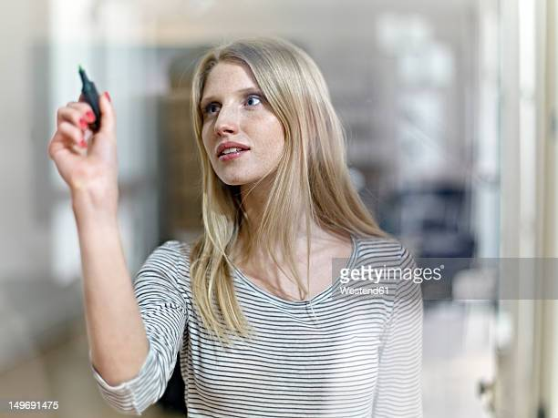 Germany, Cologne, Young woman drawing on glass